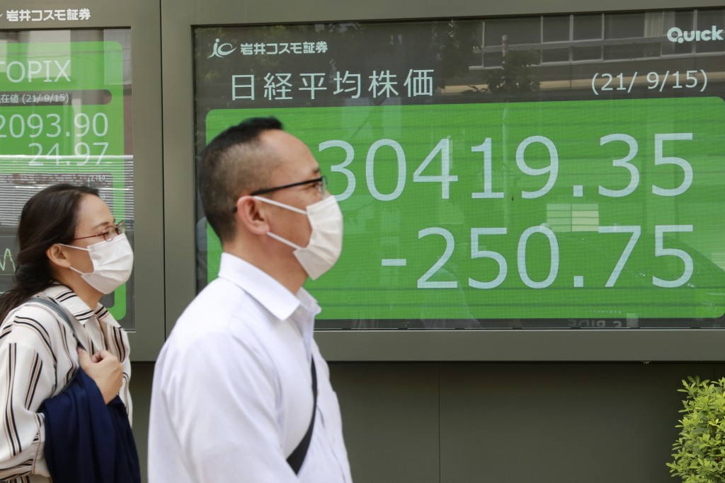 People walk by an electronic stock board of a securities firm in Tokyo, Wednesday, Sept. 15, 2021. Asian stock markets followed Wall Street down on We...