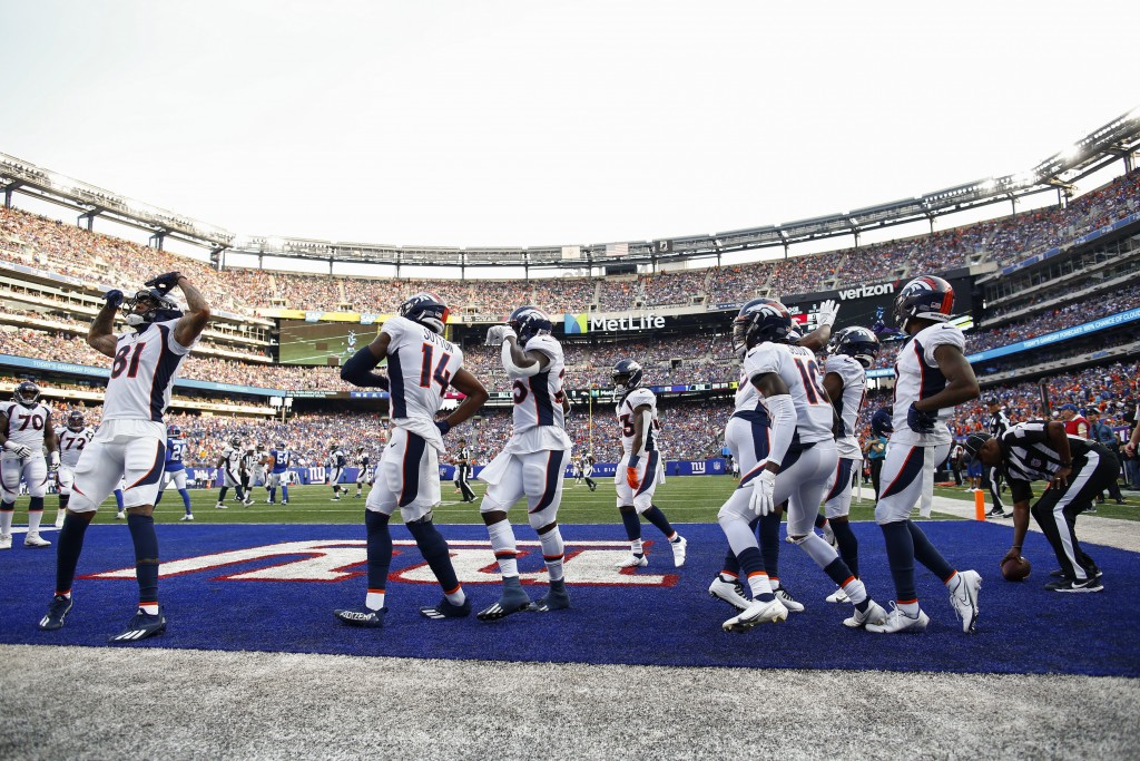 Denver Broncos wide receiver Tim Patrick (81) celebrates with teammates after scoring a touchdown during the first half of an NFL football game agains...