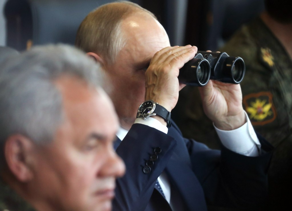 Russian President Vladimir Putin, center, watches through binoculars as Russian Defense Minister Sergei Shoigu sits near during the joint strategic ex...