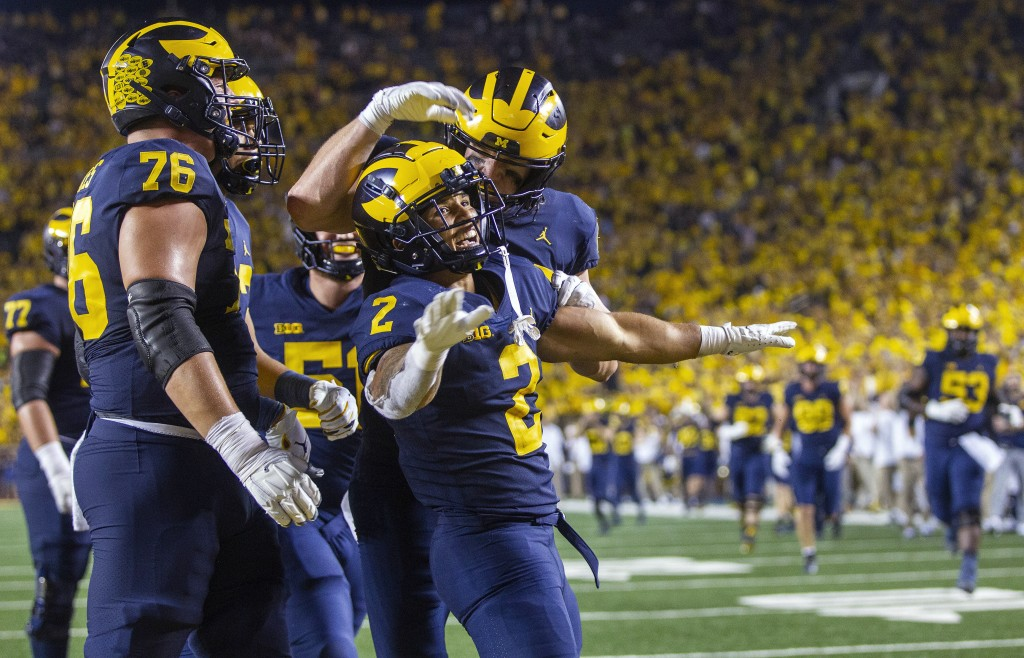 Michigan running back Blake Corum (2) celebrates a touchdown with teammates during the fourth quarter of an NCAA college football game against Washing...