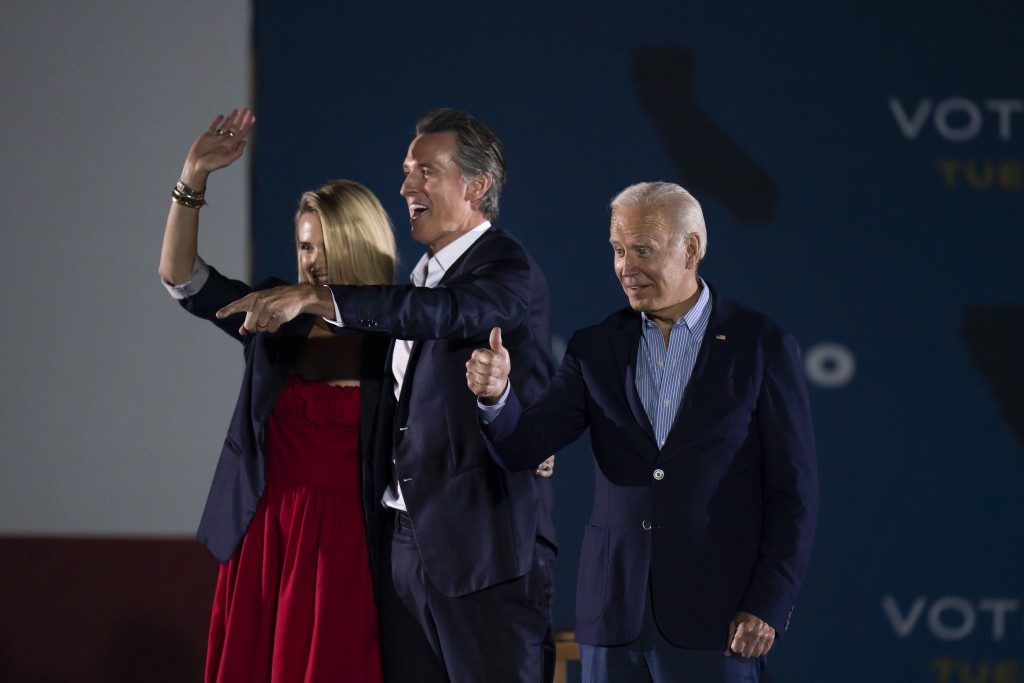 President Joe Biden, right, gives a thumb up as California Gov. Gavin Newsom, and wife, Jennifer Siebel Newsom, wave to their supporters at a rally ah...