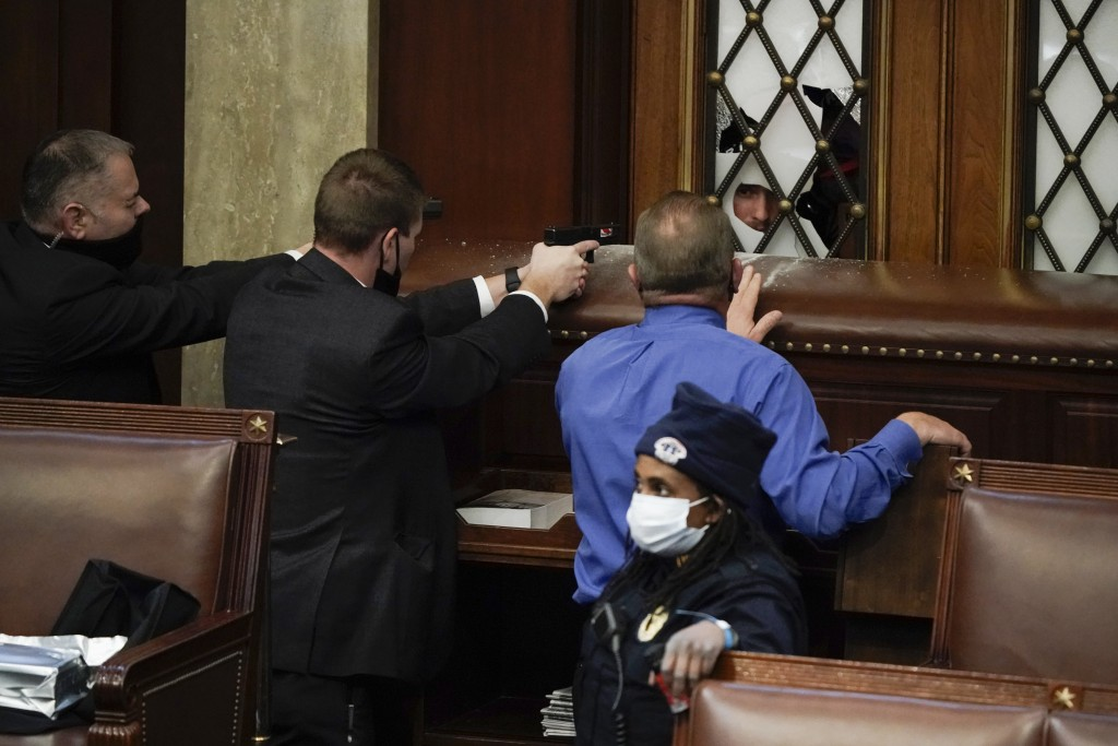 FILE - In this Jan. 6, 2021, file photo U.S. Capitol Police officers with guns drawn and Rep. Troy Nehls, R-Texas, in blue shirt, watch as insurrectio...