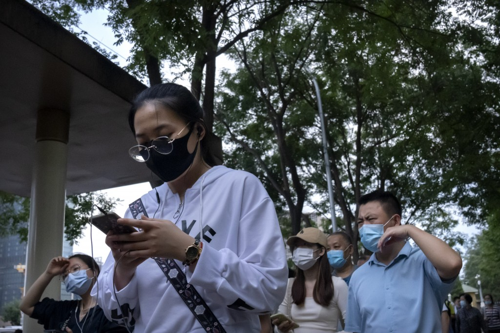 People wearing face masks to protect against COVID-19 wait in line at a bus stop in the central business district in Beijing, Thursday, Sept. 16, 2021...