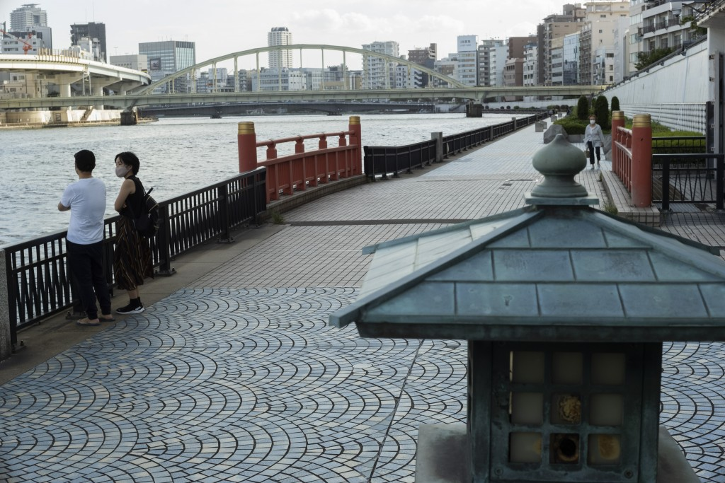 A man and a woman wearing face masks watch the Sumida River as they visit its riverside walking trail in Tokyo, Thursday, Sept. 16, 2021. (AP Photo/Hi...