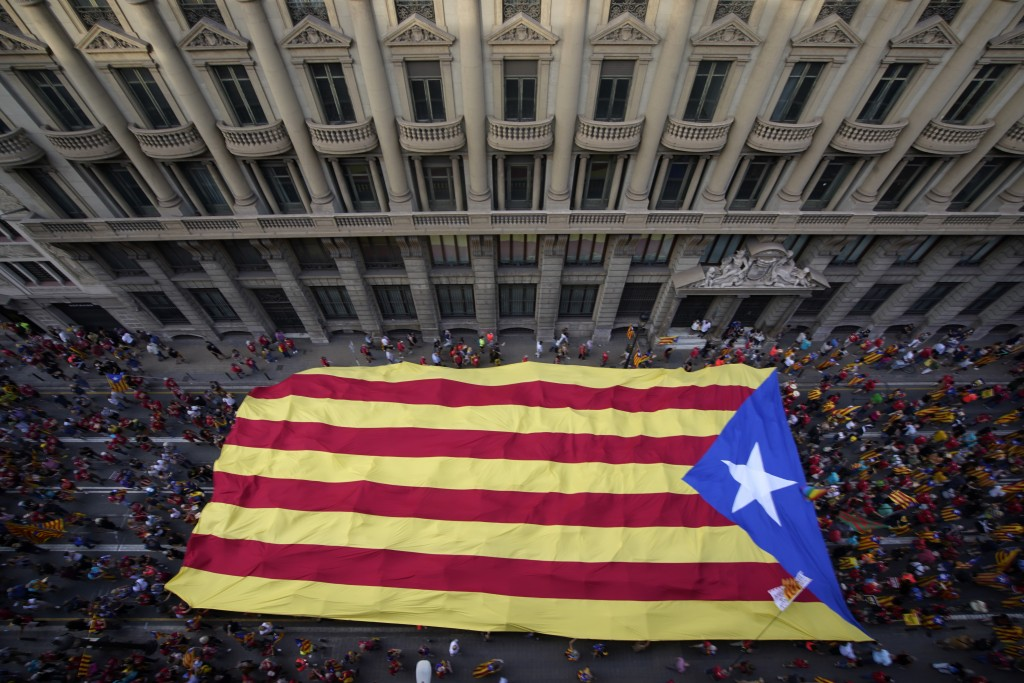 Demonstrators march holding a pro-independence flag during the Catalan National Day in Barcelona, Spain, Saturday, Sept. 11, 2021. Thousands of Catala...