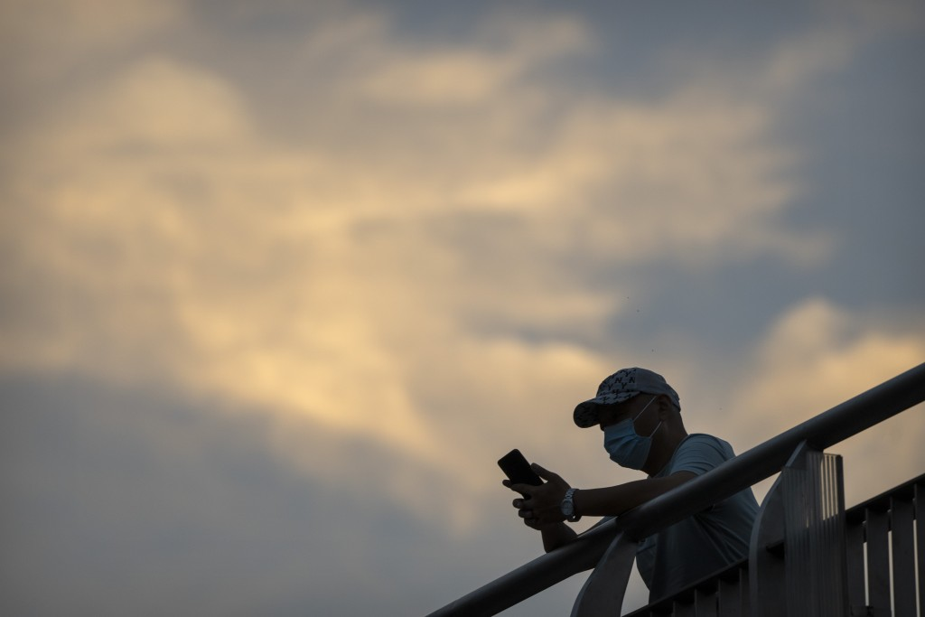 A man wearing a face mask to protect against COVID-19 stands on a pedestrian bridge in the central business district in Beijing, Thursday, Sept. 16, 2...