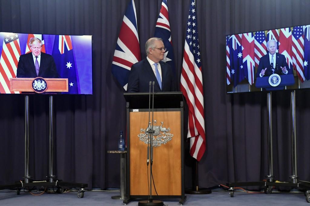 Australia's Prime Minister Scott Morrison, center, appears on stage with video links to Britain's Prime Minister Boris Johnson, left, and U.S. Preside...