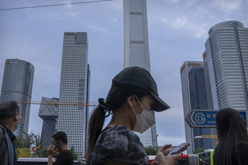 People wearing face masks to protect against COVID-19 walk along a street in the central business district in Beijing, Thursday, Sept. 16, 2021. China...