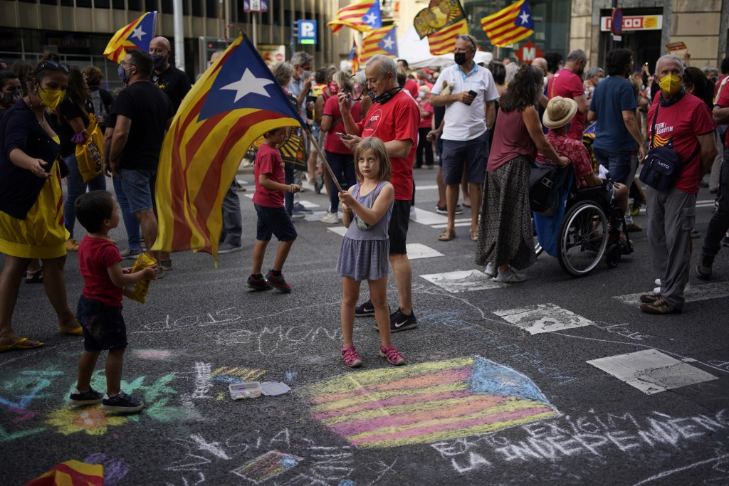 A girl waves a pro-independence flag as demonstrators march during the Catalan National Day in Barcelona, Spain, Saturday, Sept. 11, 2021. Thousands o...