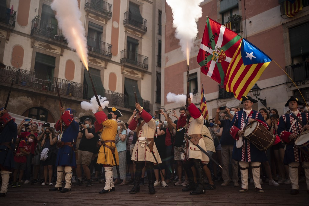 Men dressed in costume shoot their rifles during a performance to celebrate the Catalan National Day in Barcelona, Spain, Saturday, Sept. 11, 2021. Th...