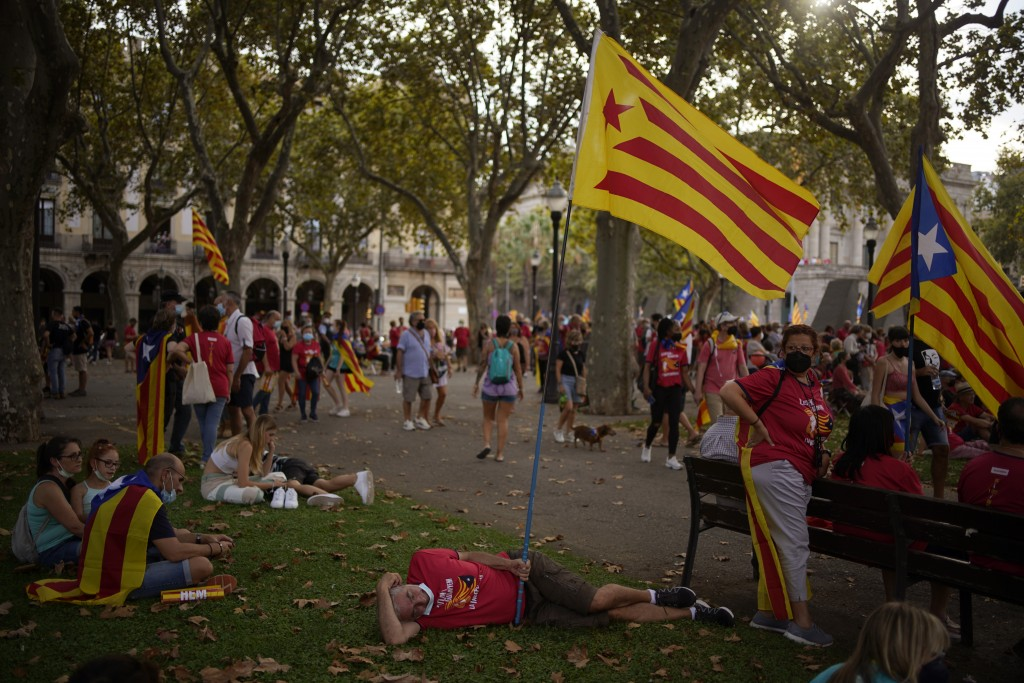 Pro-independence demonstrators rest in a park after taking part at a demonstration during the Catalan National Day in Barcelona, Spain, Saturday, Sept...
