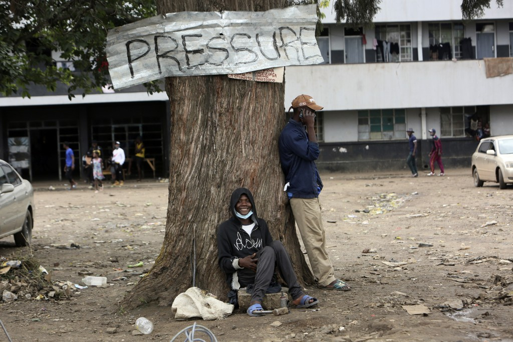 A man smiles while sitting under a tree in Harare, Zimbabwe, Thursday, Sept, 16, 2021. Zimbabwe has told all government employees to get vaccinated ag...