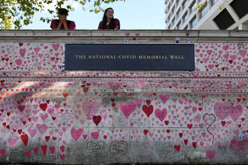 Nurses from the nearby hospital rest atop the National Covid Memory Wall in London, Thursday, Sept. 16, 2021. Although the number of people now contra...