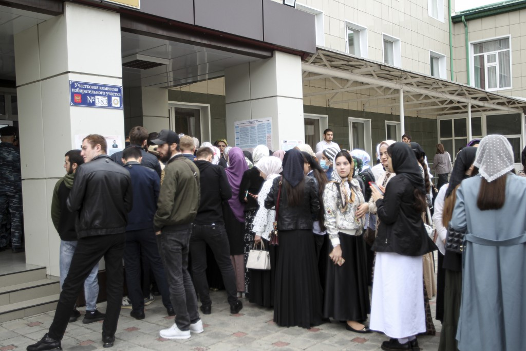 Voters gather to get in the polling station during the Parliamentary elections in Grozny, Russia, Friday, Sept. 17, 2021. Russia has begun three days ...
