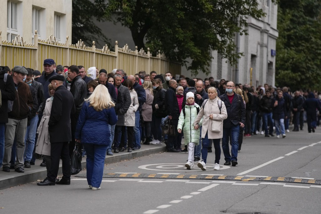 People stand in line to a polling station during parliamentary elections in Moscow, Russia, Friday, Sept. 17, 2021. Russia has begun three days of vot...