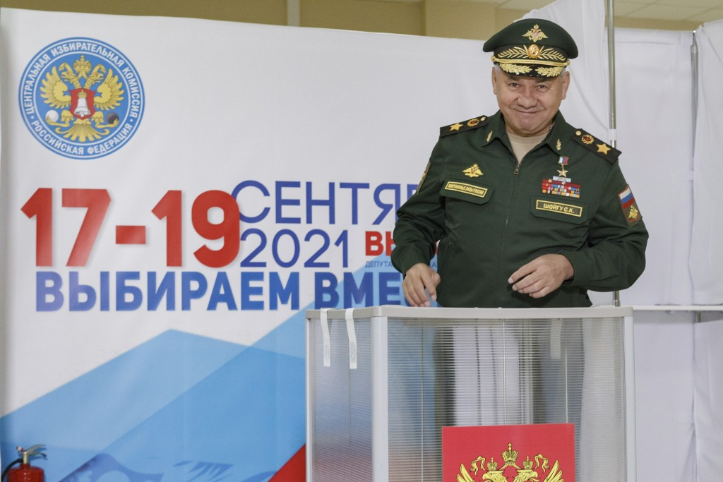 In this handout photo released by the Russian Defense Ministry Press Service, Russian Defense Minister Sergei Shoigu smiles as he casts his ballot at ...