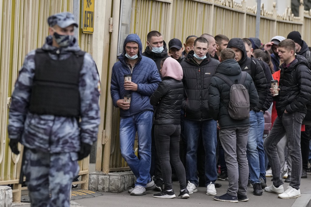 A Russian Rosguardia (National Guard) soldier guards as people queue to cast their votes at the entrance of a polling station during parliamentary ele...