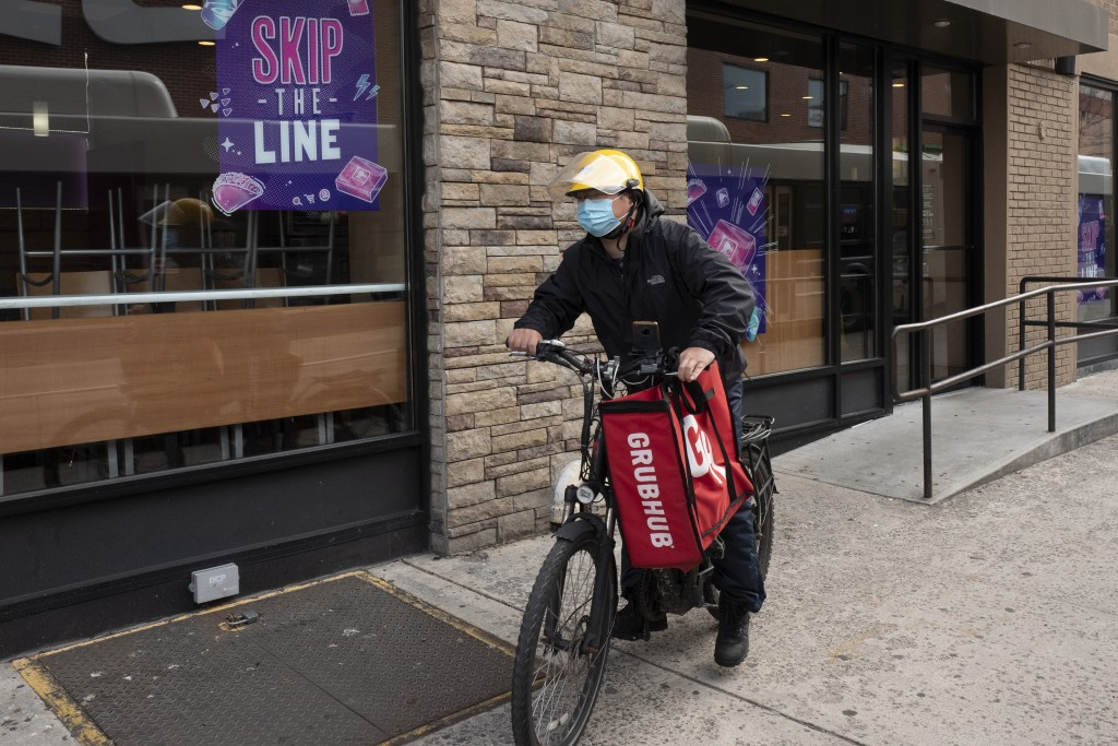 FILE - In this April 21, 2021 file photo, a delivery man bikes with a food bag from Grubhub in New York.  The three biggest food delivery companies, D...
