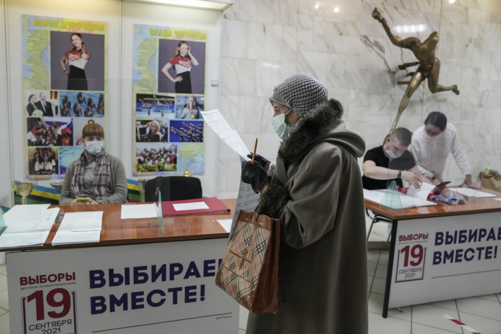 A woman prepares to cast her ballot at a polling station during a parliamentary elections in Moscow, Russia, Friday, Sept. 17, 2021. Russia has begun ...