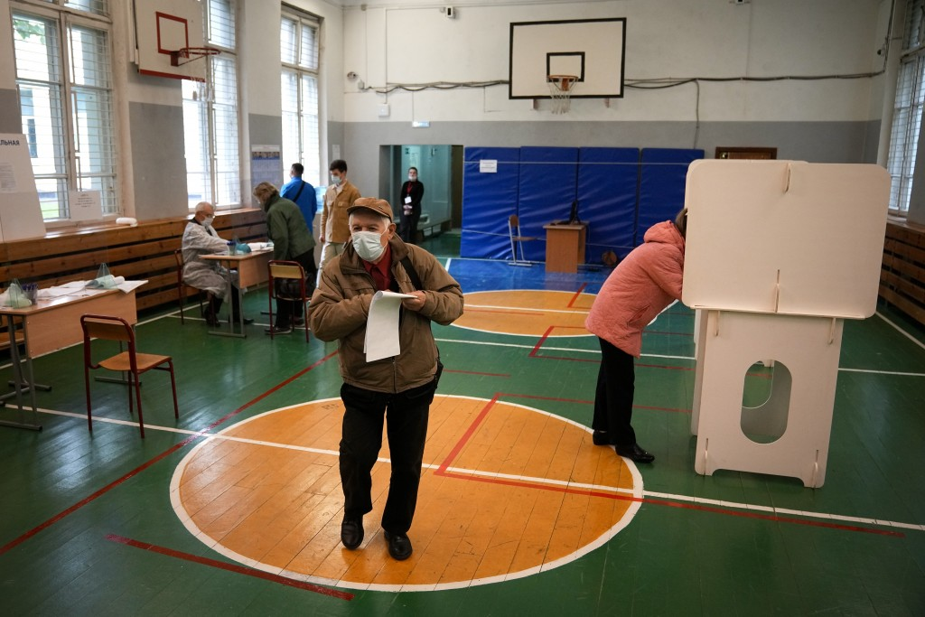 A man walks to casts his ballot at a polling station during the Parliamentary elections in Moscow, Russia, Friday, Sept. 17, 2021. Russia has begun th...