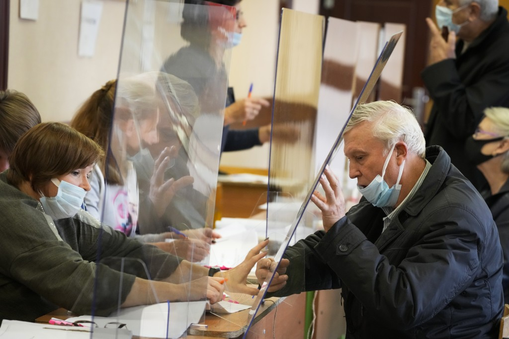 A man is handed his ballots through a safety glass protecting from coronavirus infection during the State Duma, the Lower House of the Russian Parliam...