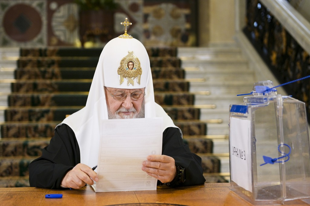 In this photo released by Russian Orthodox Church Press Service, Russian Orthodox Church Patriarch Kirill reads his ballot during the Parliamentary el...