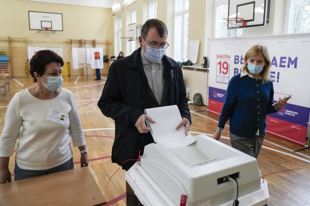A man casts his ballot at a polling station during the parliamentary elections in Moscow, Russia, Friday, Sept. 17, 2021. Russia has begun three days ...