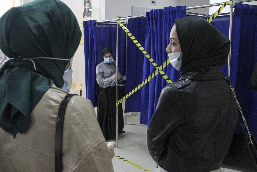 Chechen women wait to fill their ballots in a voting booth at a polling station during the Parliamentary elections in Grozny, Russia, Friday, Sept. 17...