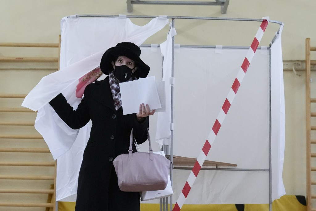 A woman prepares to cast her ballot at a polling station during the parliamentary elections in Moscow, Russia, Friday, Sept. 17, 2021. Russia has begu...