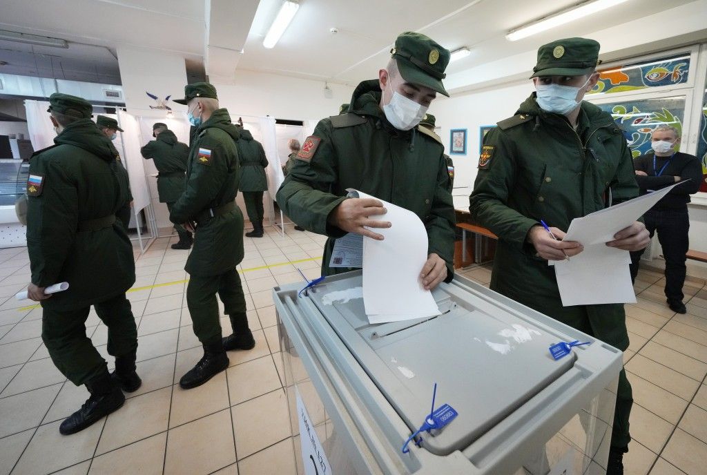 Russian Army soldiers cast their ballots during the State Duma, the Lower House of the Russian Parliament and local parliaments elections at a polling...