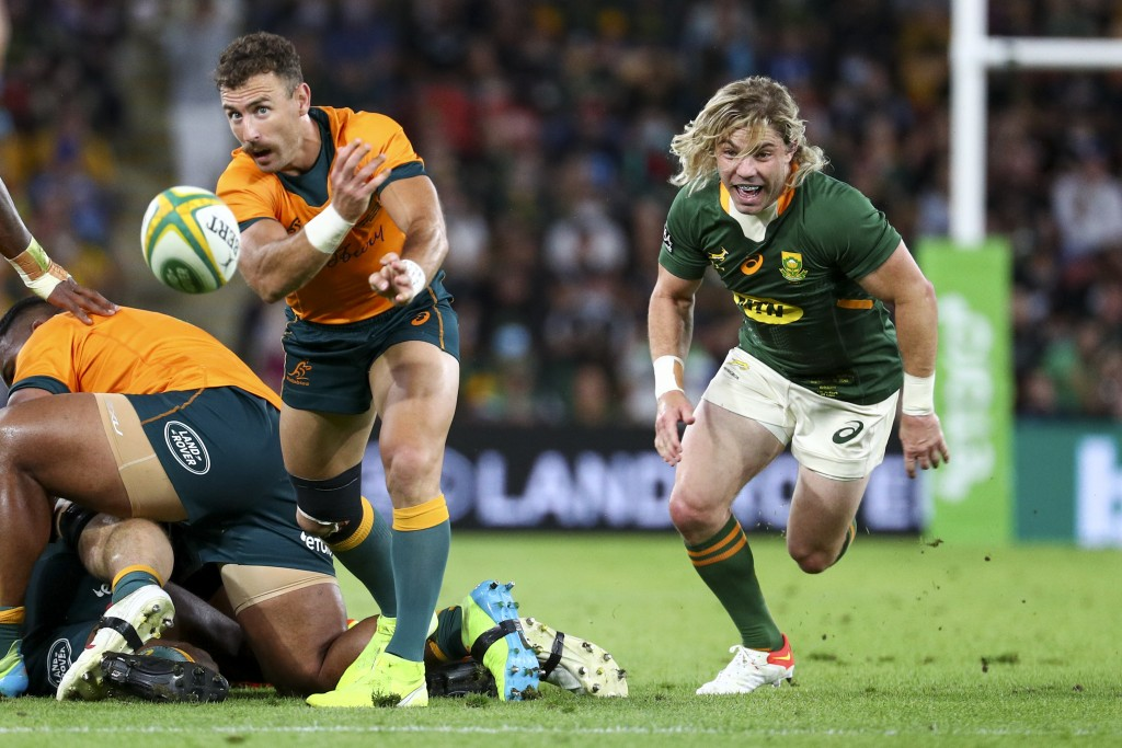 Australia's Nic White passes the ball as South Africa's Faf de Klerk chases during the Rugby Championship test match between the Springboks and the Wa...