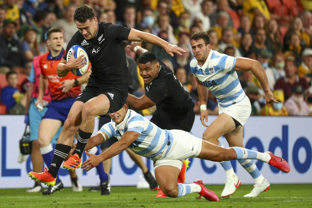 New Zealand's Will Jordan leaps clear of the defense during the Rugby Championship test match between the All Blacks and the Pumas in Brisbane, Austra...