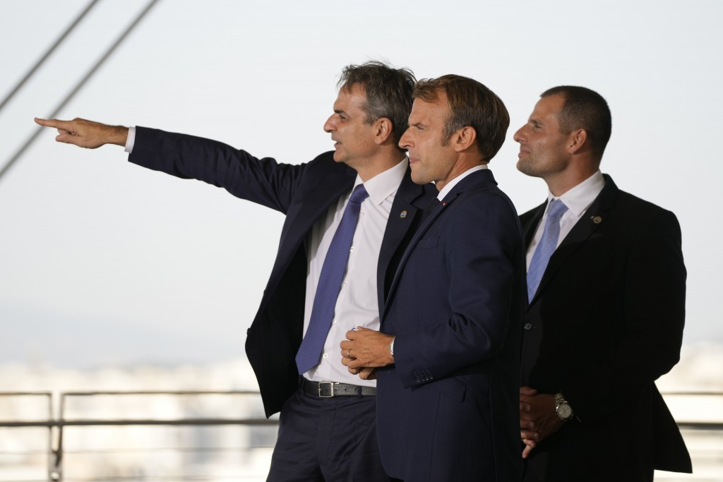 Greek Prime Minister Kyriakos Mitsotakis, left, shows the view of the Greek capital to his Maltese counterpart Robert Abela, right, and French Preside...