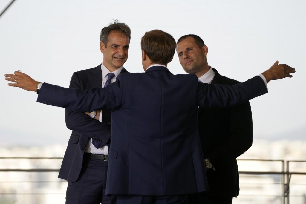 Greek Prime Minister Kyriakos Mitsotakis, left, and his Maltese counterpart Robert Abela, right, listen to French President Emmanuel Macron during the...