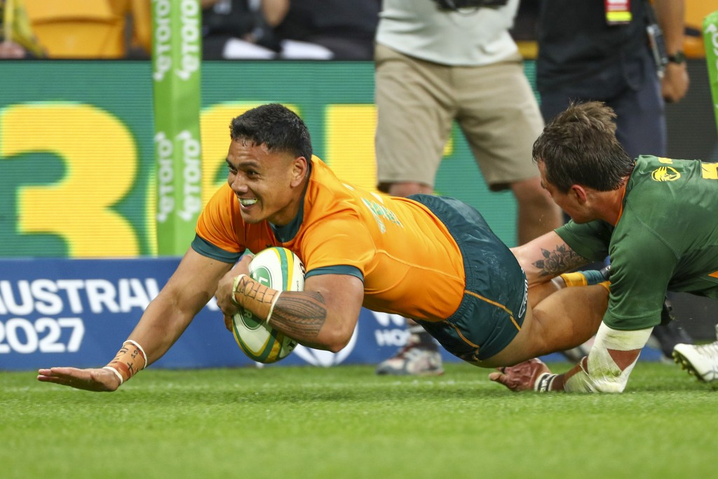 Australia's Len Ikitau, left, scores a try as South Africa's Franco Mostert attempts a tackle during the Rugby Championship test match between the Spr...