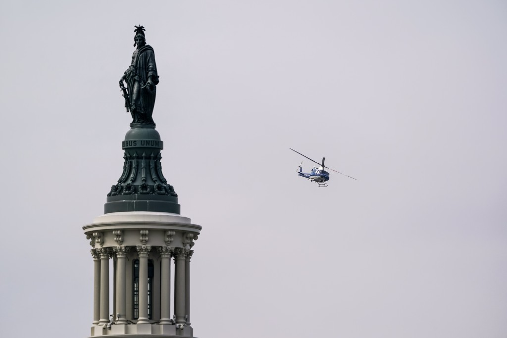 A U.S. Park Police helicopter is seen flying near the Capitol as it circles the southwest quadrant of Washington to monitor a fire in a building under...