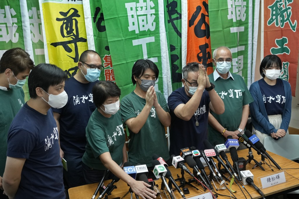 Hong Kong Confederation of Trade Unions President Joe Wong Nai-yuen, third from right, with deep blue T-shirt, gestures while posing for a photo with ...