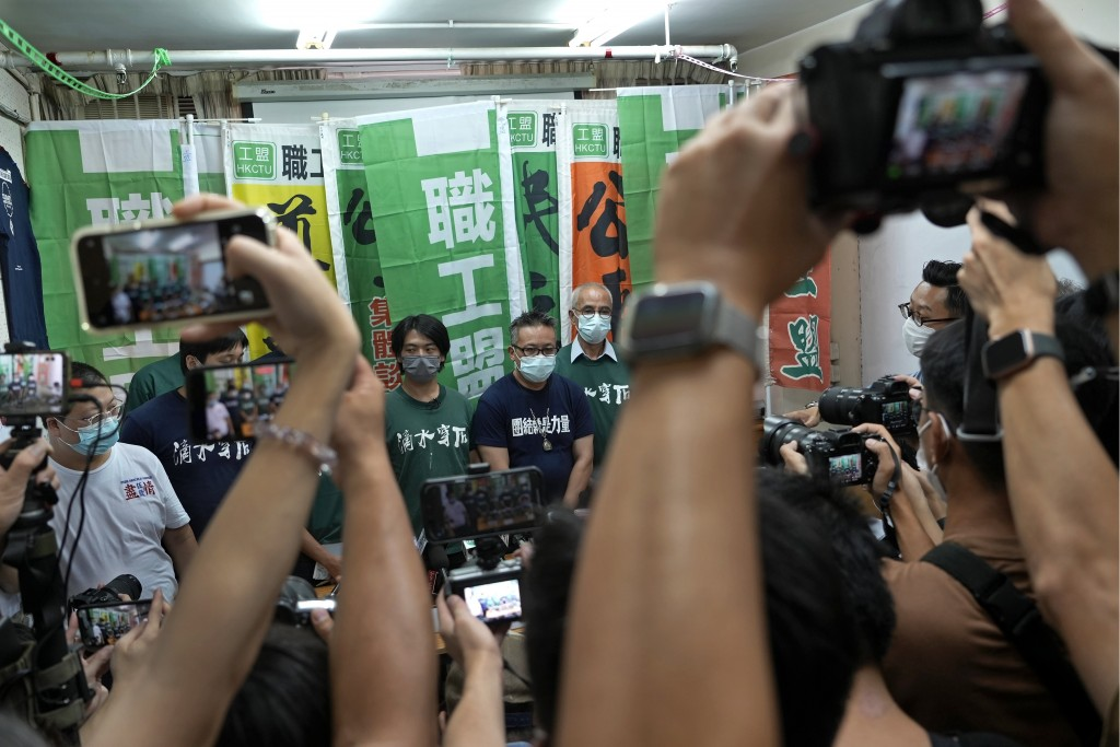 Hong Kong Confederation of Trade Unions President Joe Wong Nai-yuen, center with deep blue T-shirt, poses with other members before a news conference ...