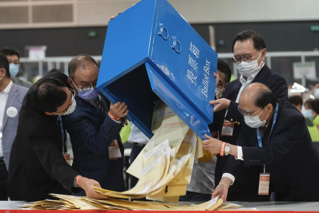 Erick Tsang, second left, Secretary for Constitutional and Mainland Affairs Bureau, helps officials pour out ballots from a box at a counting center i...