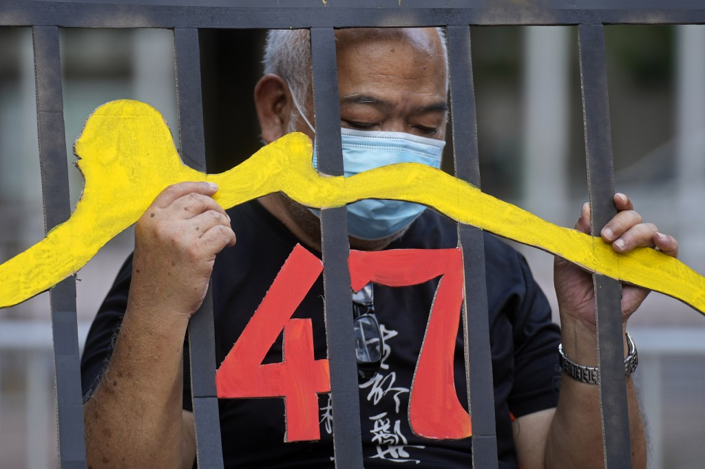 A protester stands behind a mock prison during a protest against an election committee that will vote for the city's leader in Hong Kong Sunday, Sept....