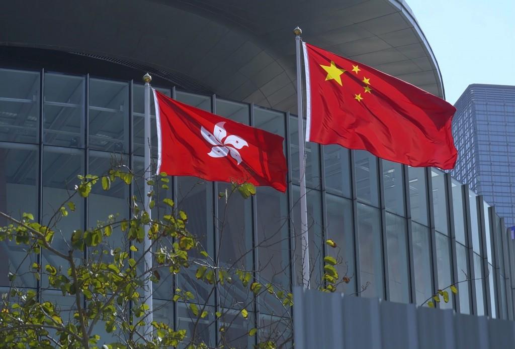 FILE - In this April 13, 2021, file photo, China's national flag, right, and Hong Kong's flag flutter at the Legislative Council in Hong Kong. Hong Ko...