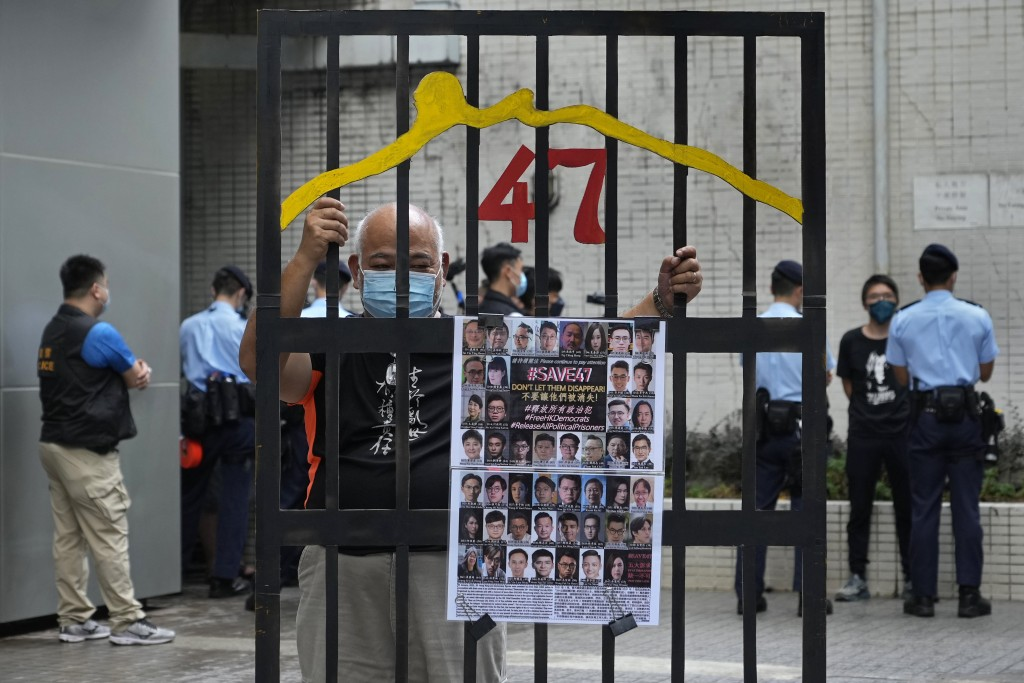A protester stands behind a mock prison while police officers do search to other protesters during a protest against an election committee that will v...