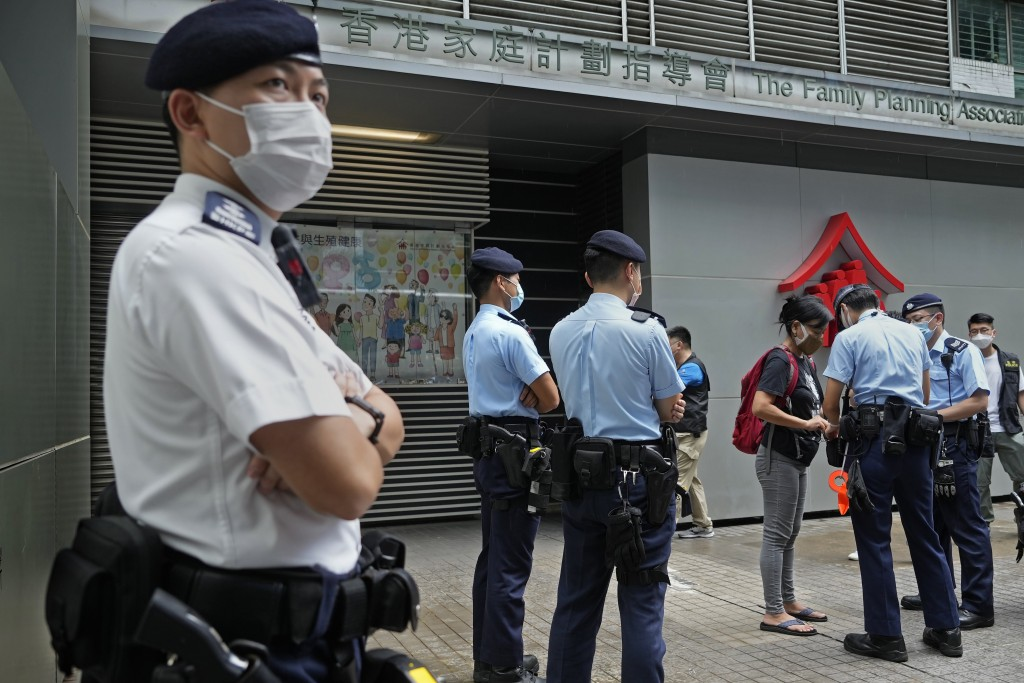 Chen Baoying, right with red backpack, one of the four protesters is searched by police officers during a protest against an election committee in Hon...