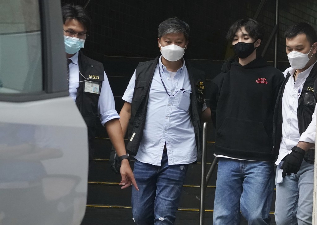 Wong Yat-chin, second from right, leader of Hong Kong Student Politicism escorted after being   arrested by national security police in Hong Kong, Mon...