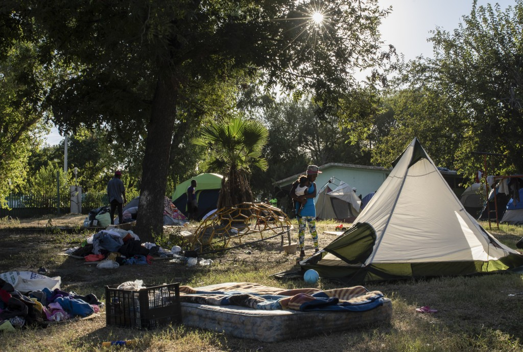 A migrant holds a child at an encampment in Ciudad Acuna, Mexico, Friday, Sept. 24, 2021, across the Rio Grande from Del Rio, Texas. No migrants remai...