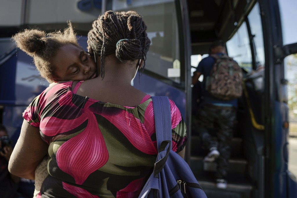FILE - In this Sept. 22, 2021, file photo a child sleeps on the shoulder of a woman as they prepare to board a bus to San Antonio moments after a grou...