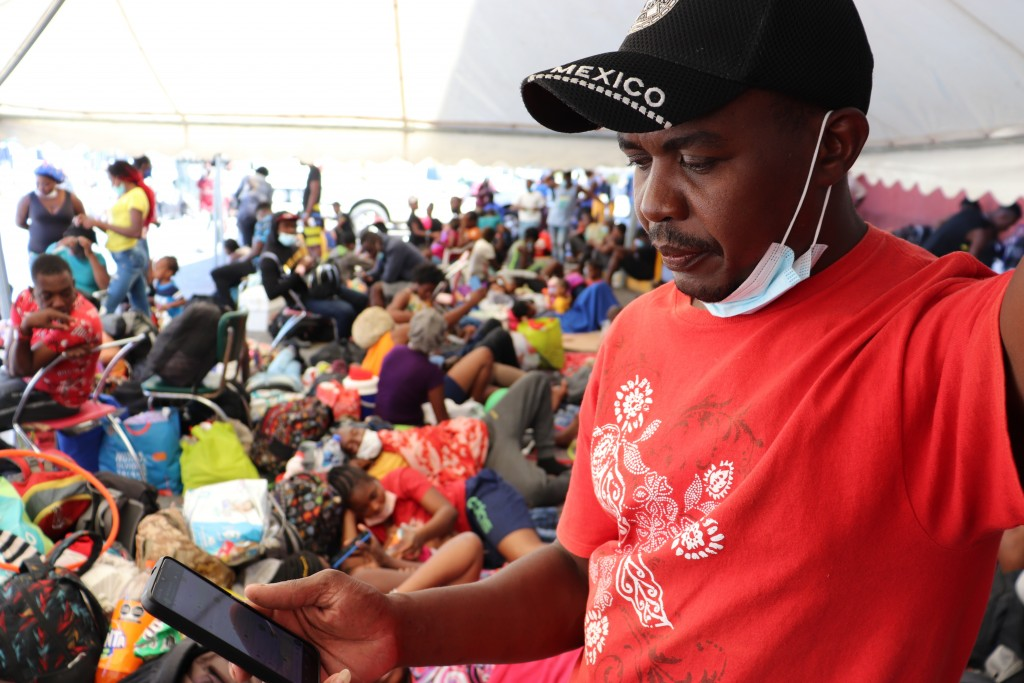 Selomourd Menrrivil, from Cap-Haitien, Haiti, looks at his cell phone as he gathers with other migrants in Monterrey, Mexico, Thursday, Sept. 23, 2021...