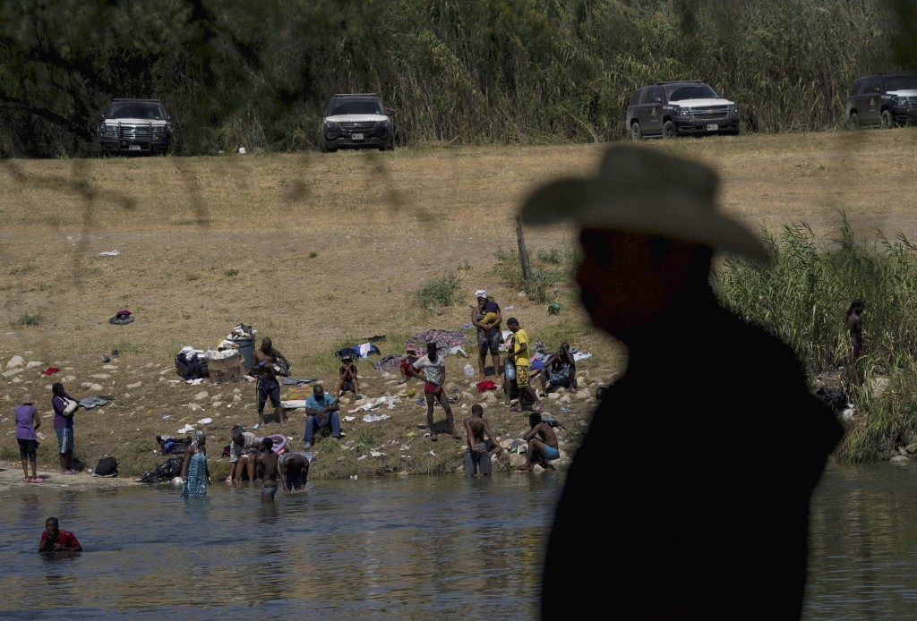 FILE - In this Sept. 22, 2021, file photo migrants, many from Haiti, wade across the Rio Grande from Del Rio, Texas, to return to Ciudad Acuna, some t...