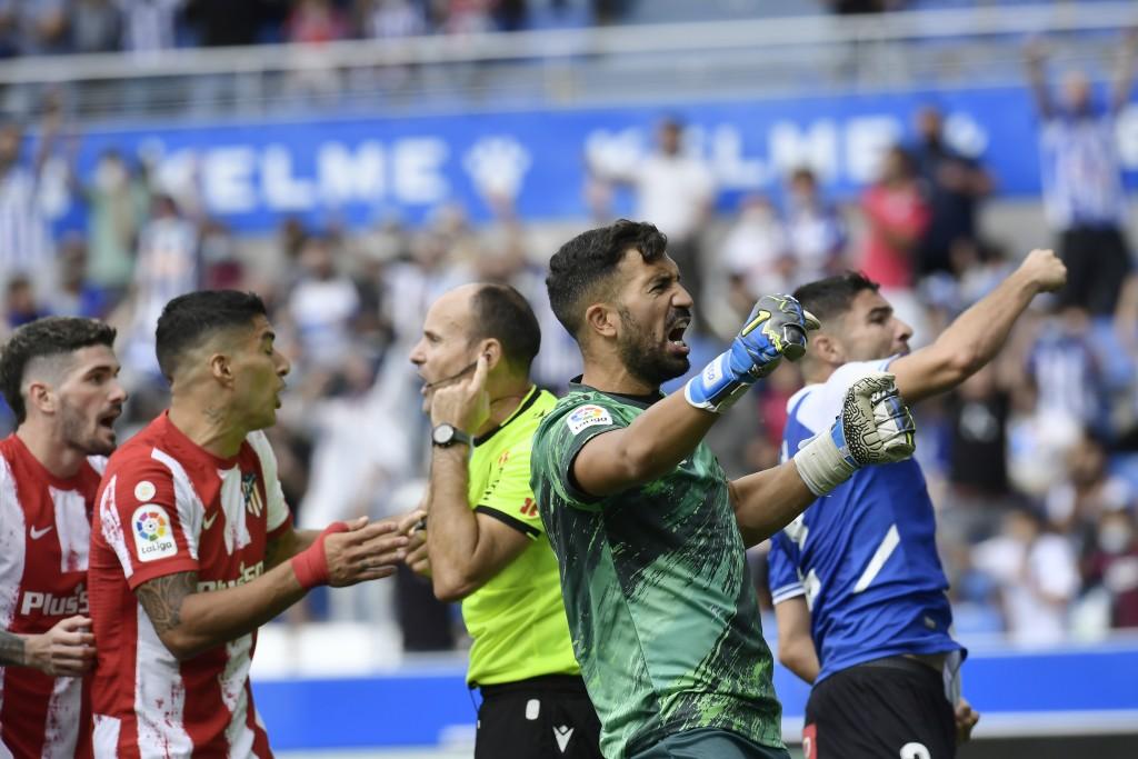 Atletico Madrid's Rodrigo De Paul, left and Luis Suarez argue with the referee as Alaves' goalkeeper Fernando Pacheco and Tachi, right, celebrate afte...