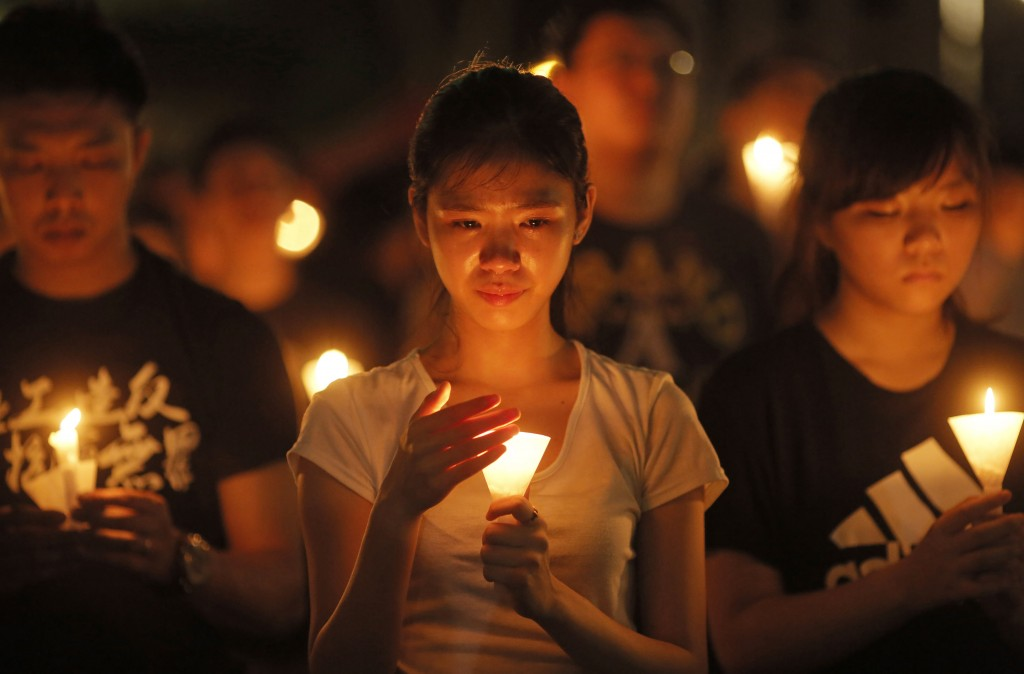 A young woman holds a candle at avigil at Victoria Park in Hong Kong.(AP Photo)